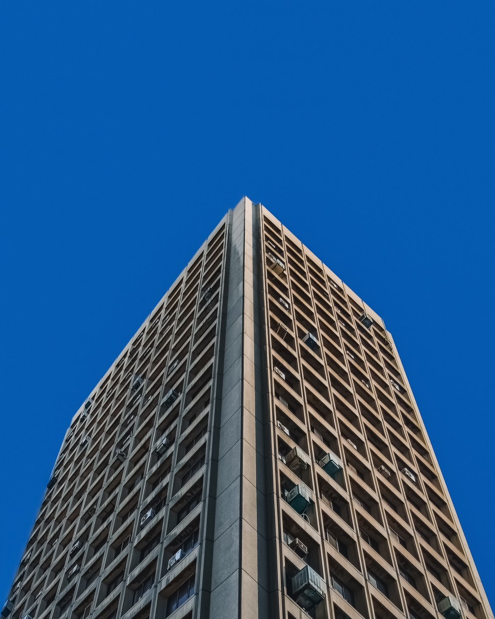 low angle photography of gray concrete building under blue sky during daytime