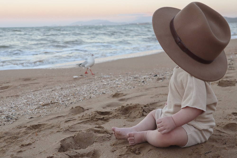child in white long sleeve shirt and brown hat sitting on brown sand beach during daytime