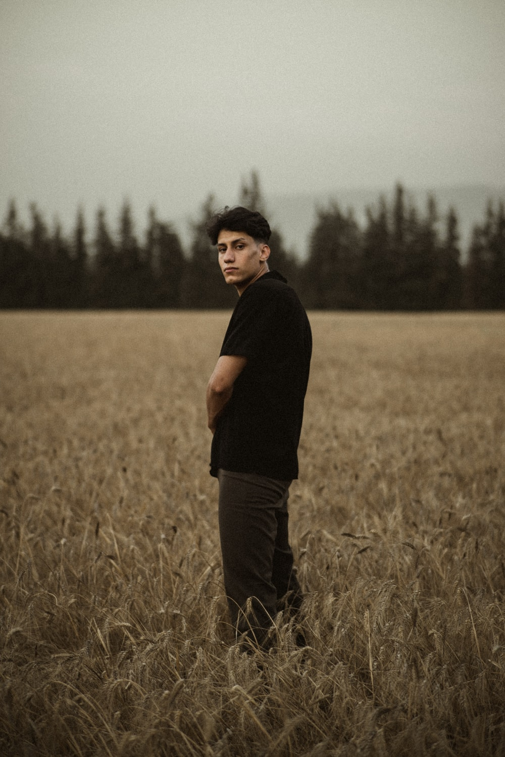 man in black t-shirt standing on brown grass field during daytime