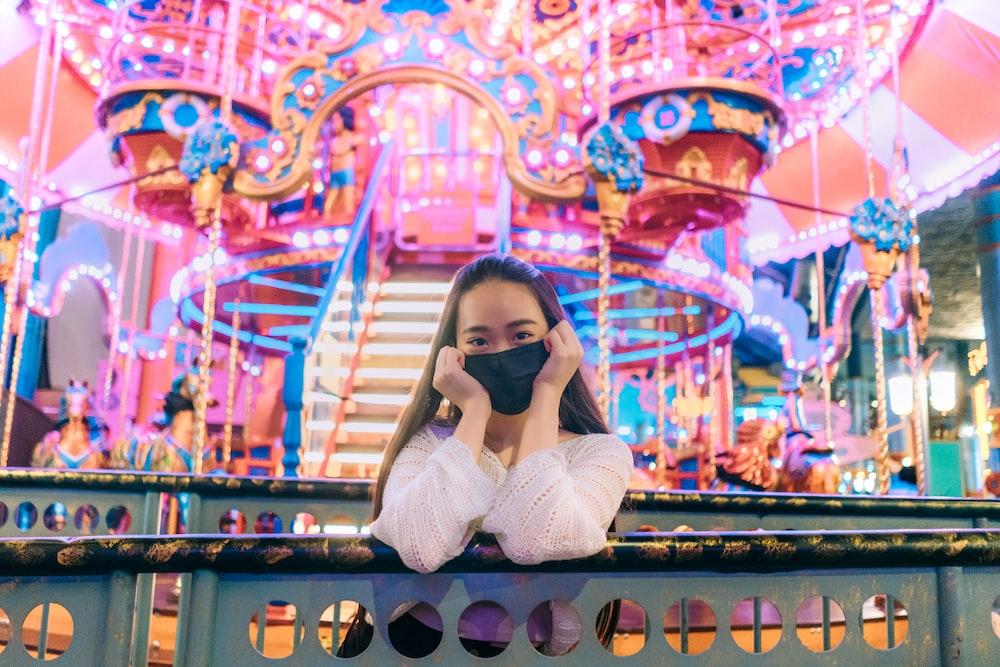 woman in white long sleeve shirt taking photo of carousel