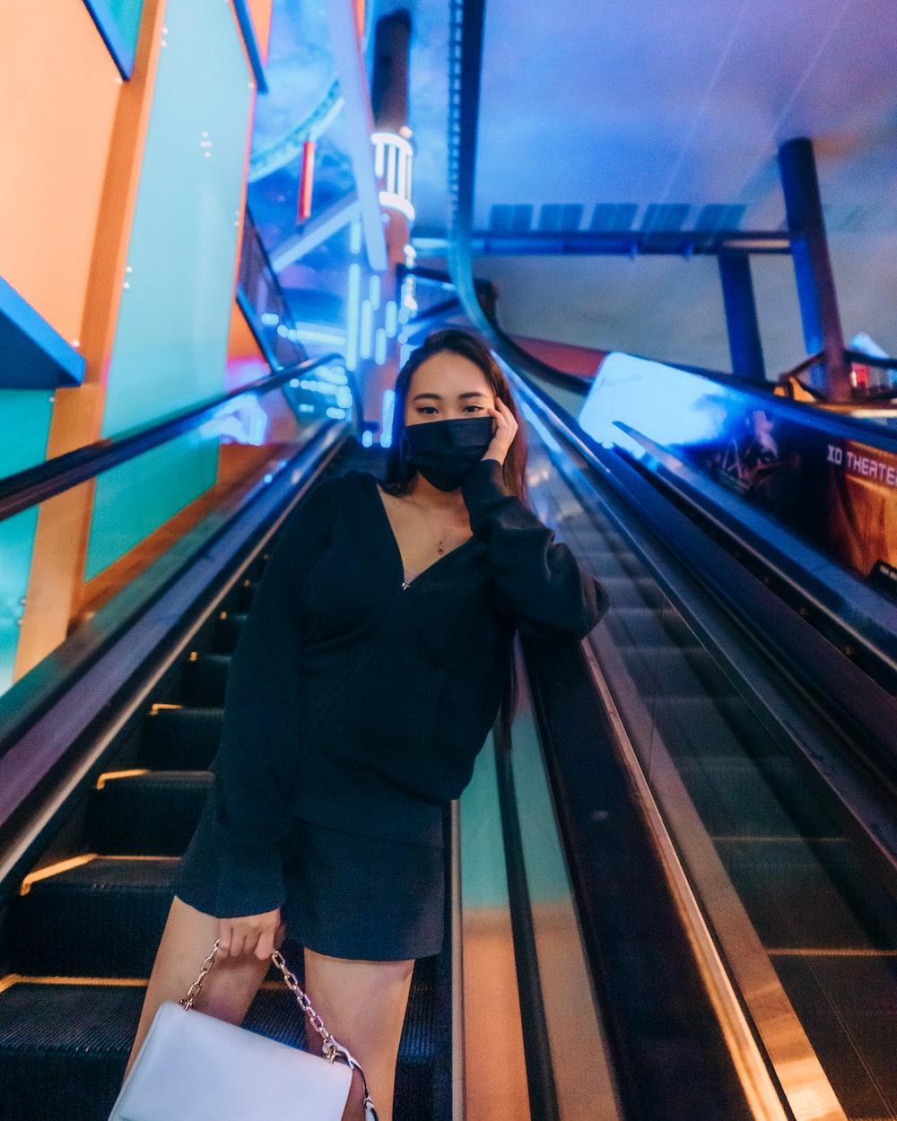 woman in black coat standing on escalator