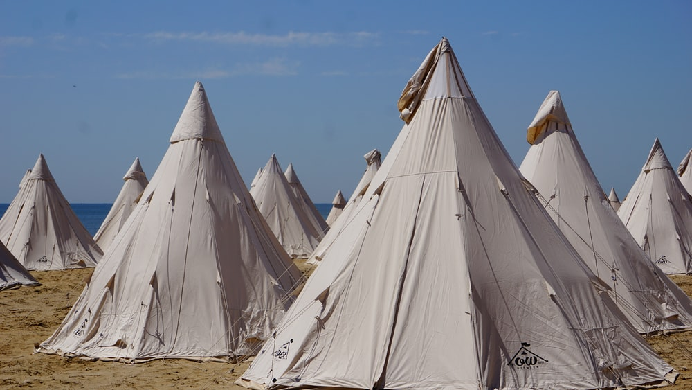 white tent on brown sand under blue sky during daytime