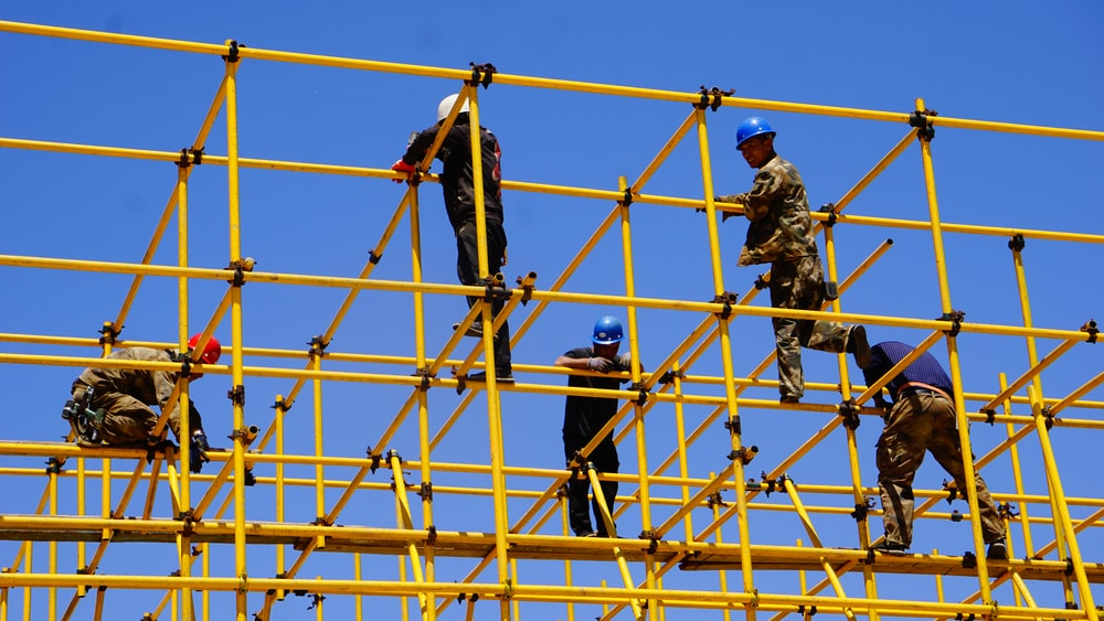 3 men standing on yellow metal fence during daytime