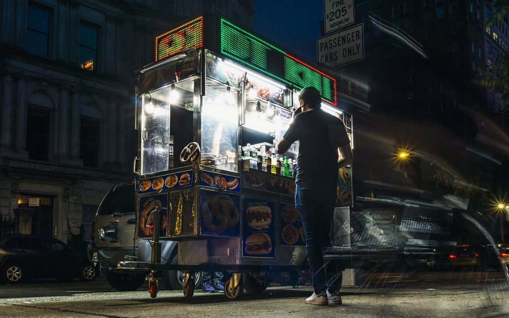 man in black jacket standing beside blue and yellow food cart