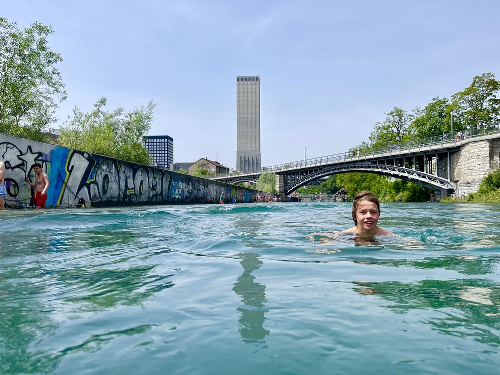 woman in swimming pool near bridge during daytime