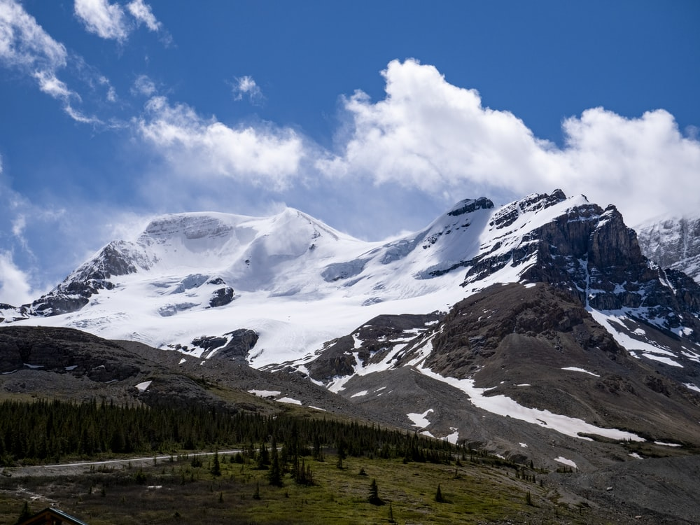 green trees and white snow covered mountain under blue sky and white clouds during daytime