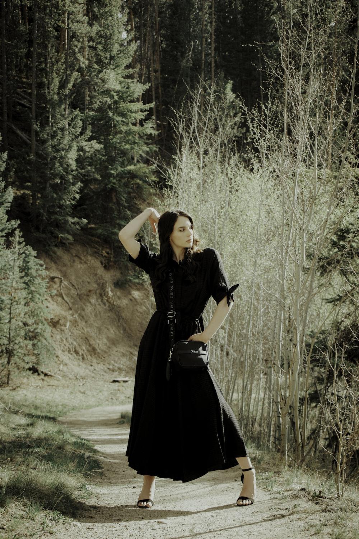 woman in black dress standing on dirt road