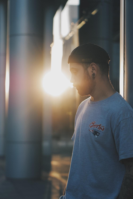 man in white crew neck t-shirt standing near glass window