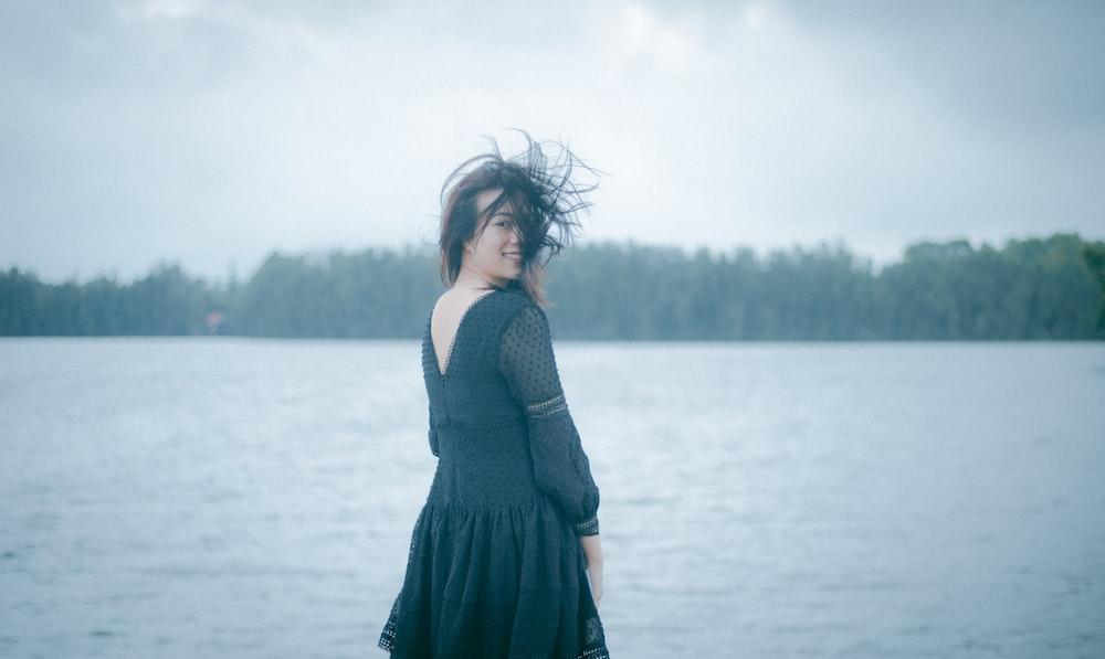woman in black dress standing on water