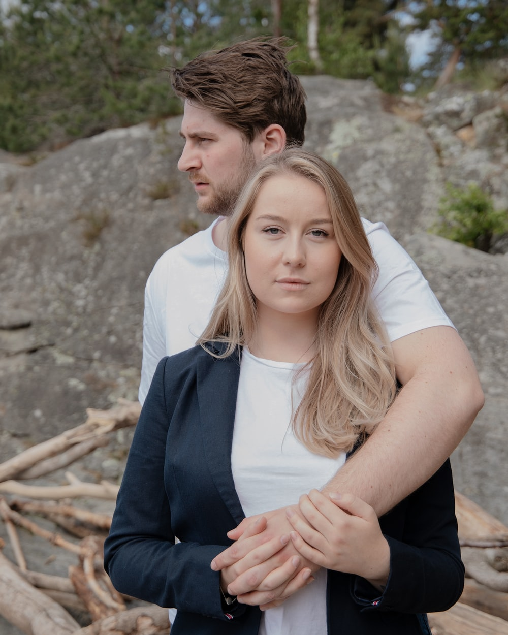 man in black suit hugging woman in white sleeveless dress