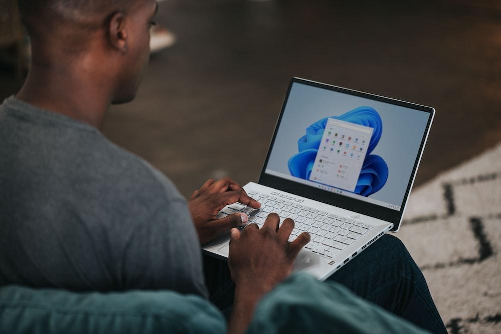 man in gray long sleeve shirt using Windows 11 computer