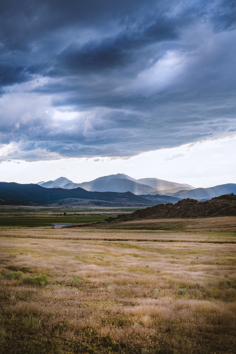 brown grass field near mountains under white clouds and blue sky during daytime