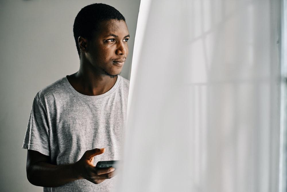 man in gray crew neck shirt standing beside white curtain