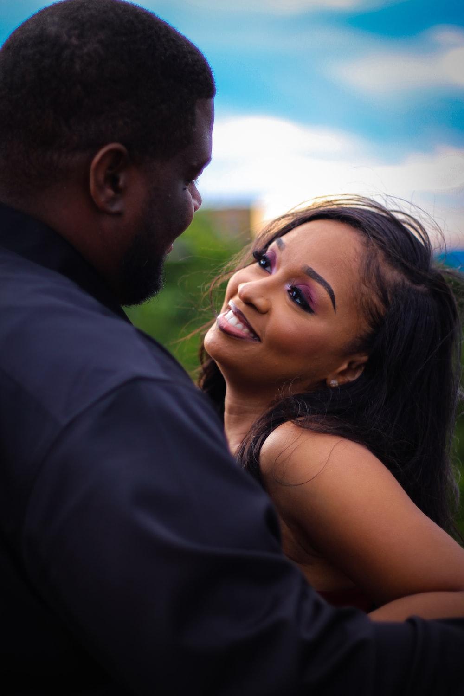 man in black shirt kissing woman in black tank top