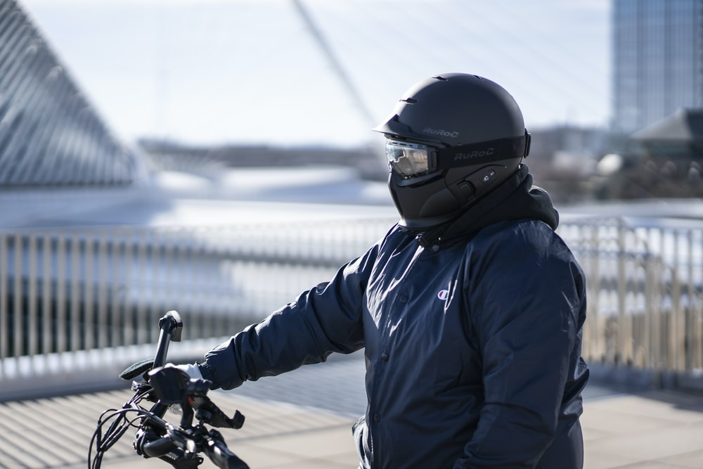 man in blue jacket riding motorcycle