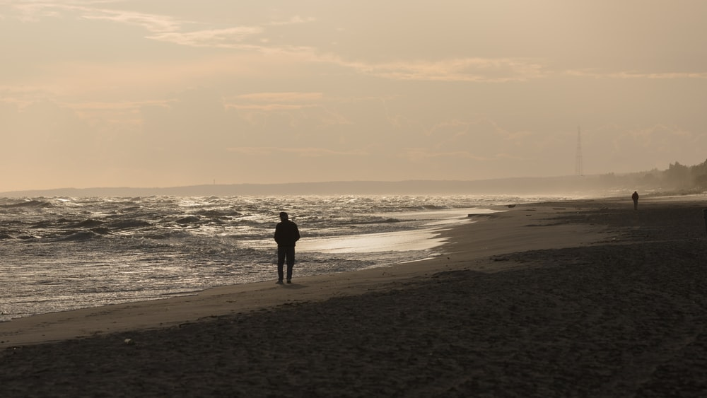 silhouette of man and woman walking on beach during daytime
