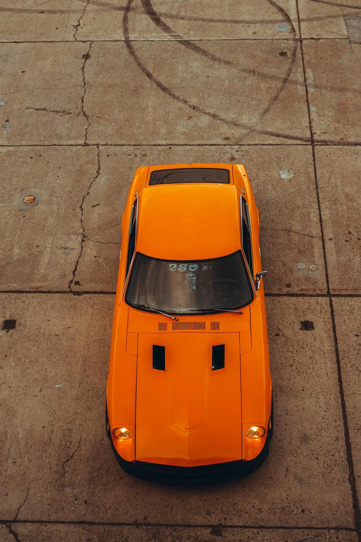 orange car on gray concrete road