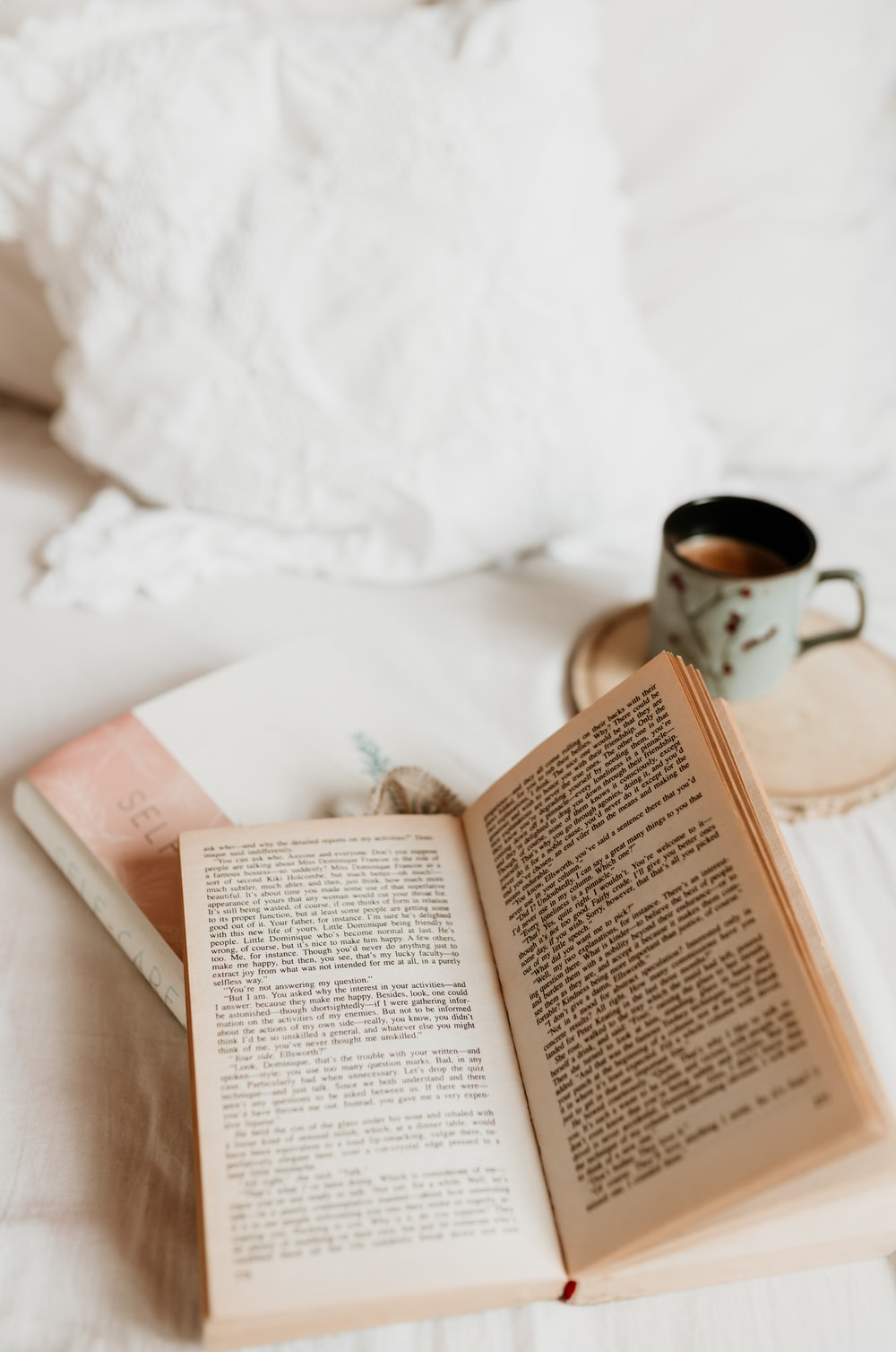 white book page beside white ceramic mug