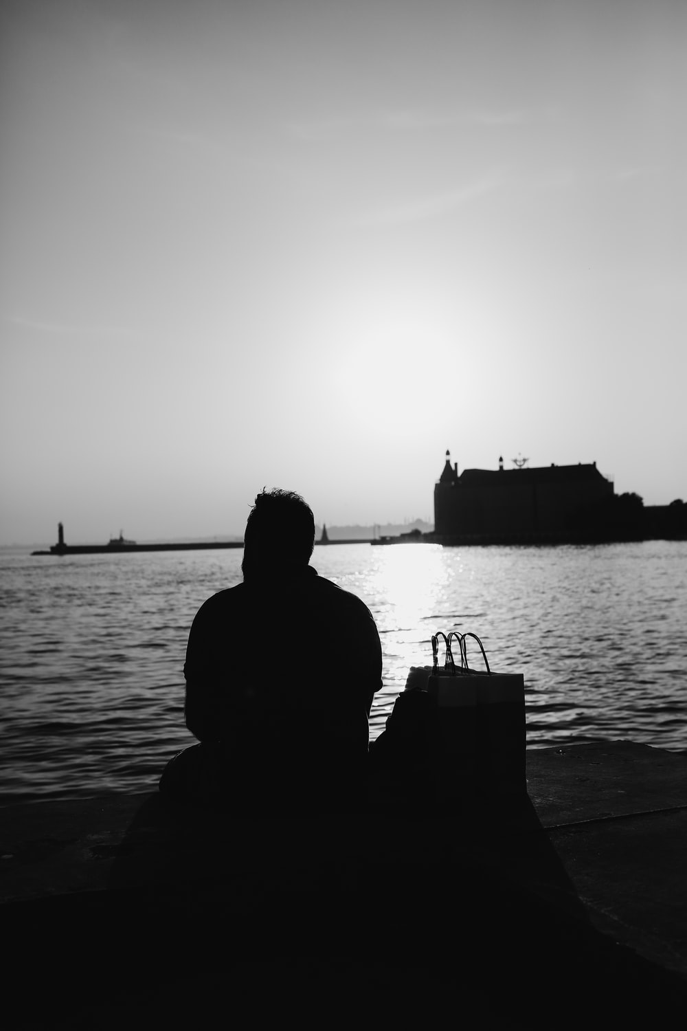 silhouette of woman sitting on chair near body of water during sunset