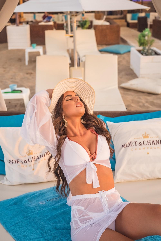 woman in white bikini top wearing white sun hat
