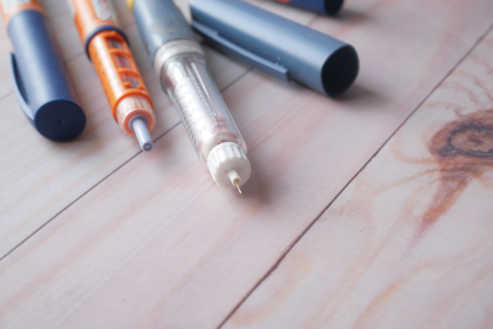 Insulin pens on wooden background, close up
