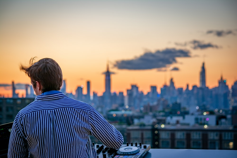 man in blue and white striped shirt looking at city skyline during daytime