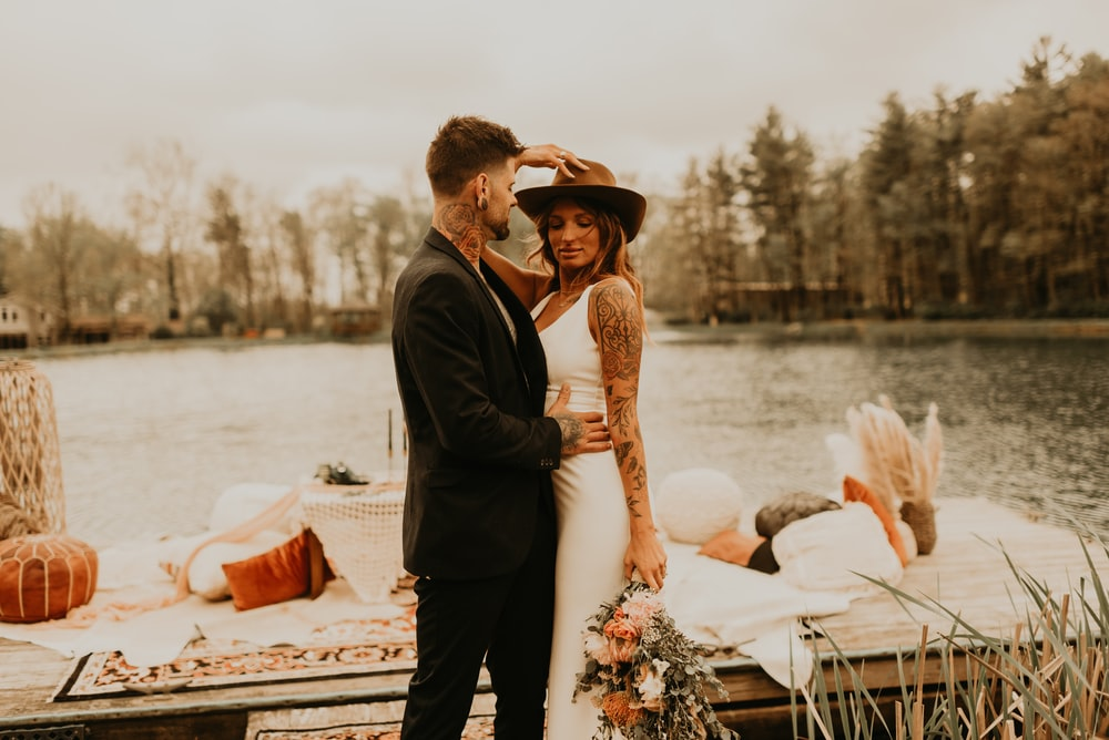 man and woman standing on dock during daytime