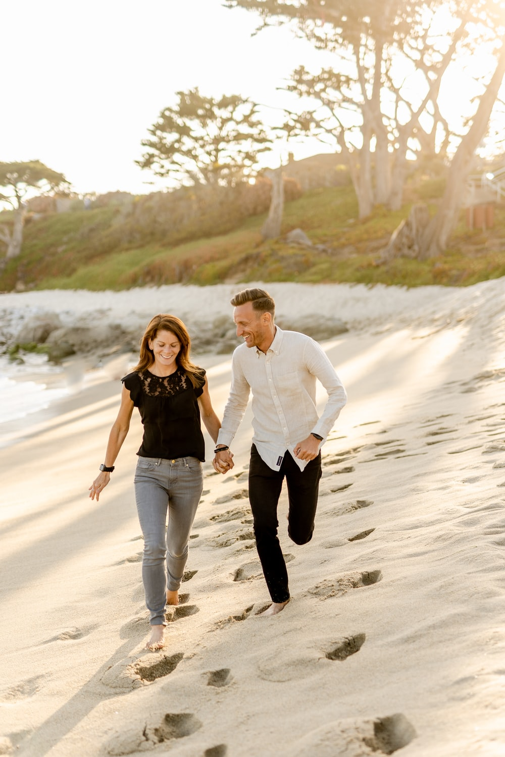 man in white dress shirt and woman in black dress walking on beach during daytime