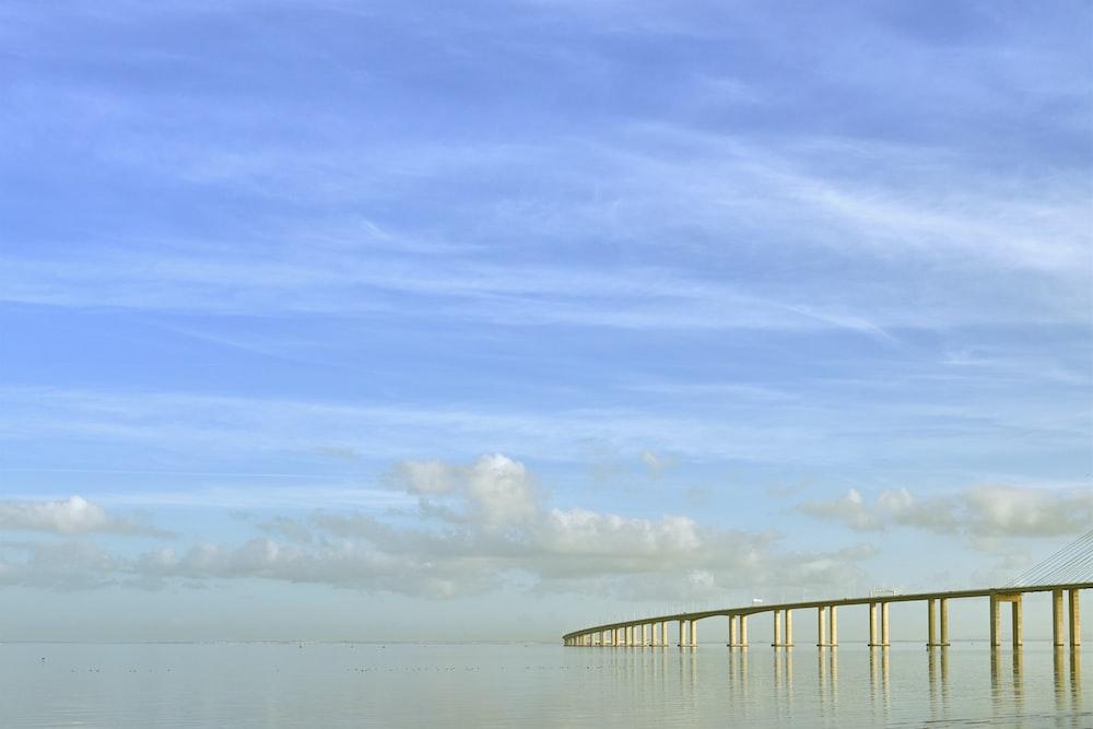 white bridge over the sea under blue sky