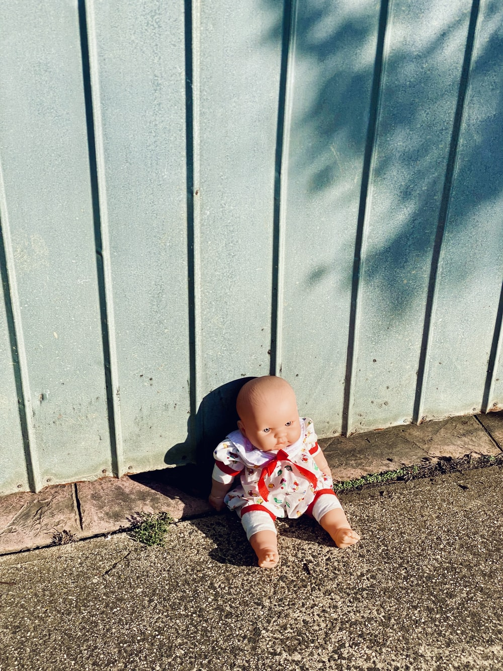 baby in white and red shirt and pants sitting on brown dirt