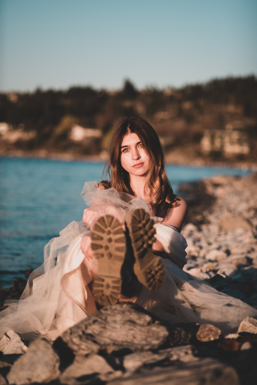 woman in white dress sitting on rock near body of water during daytime