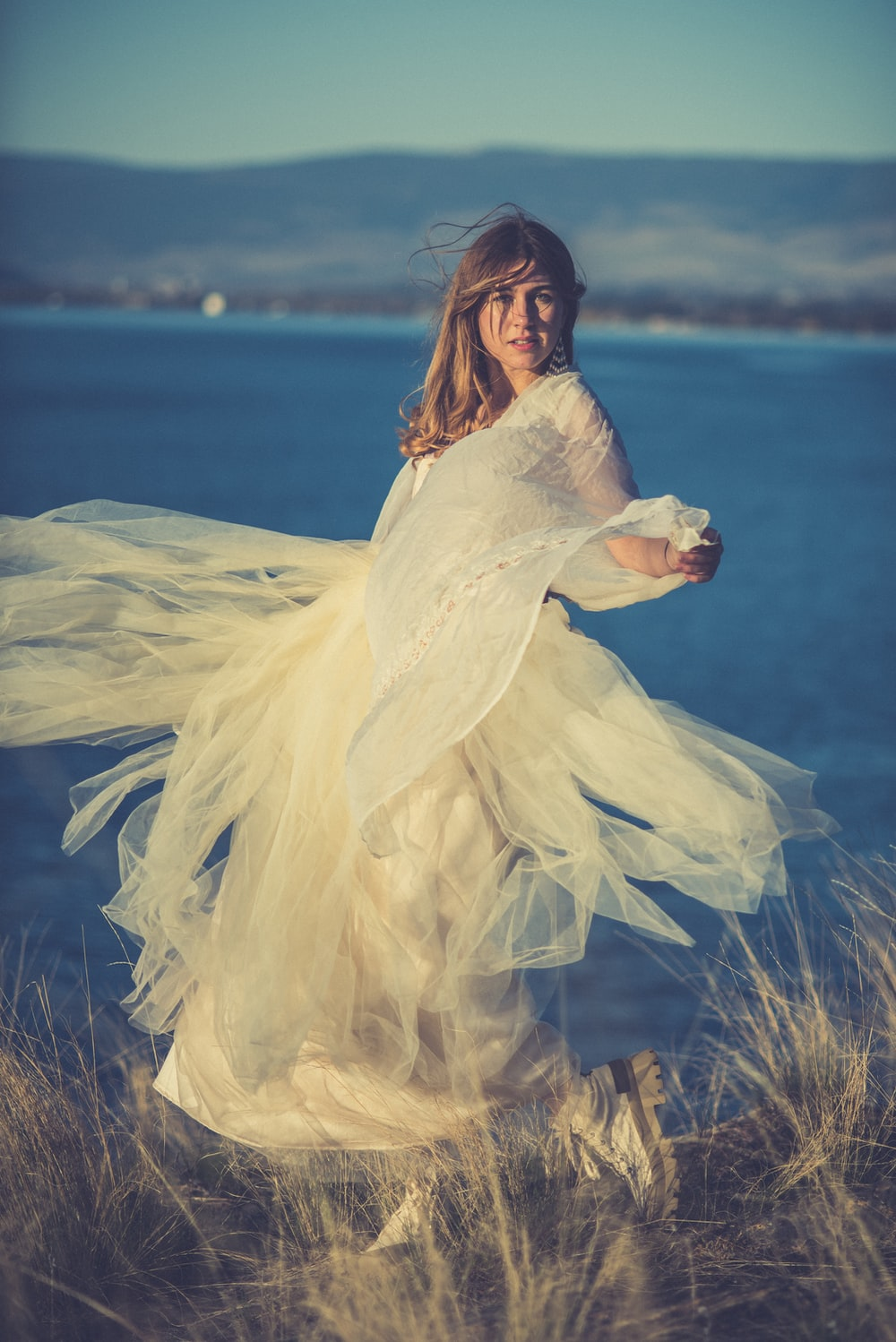 woman in white dress standing on brown grass field near body of water during daytime