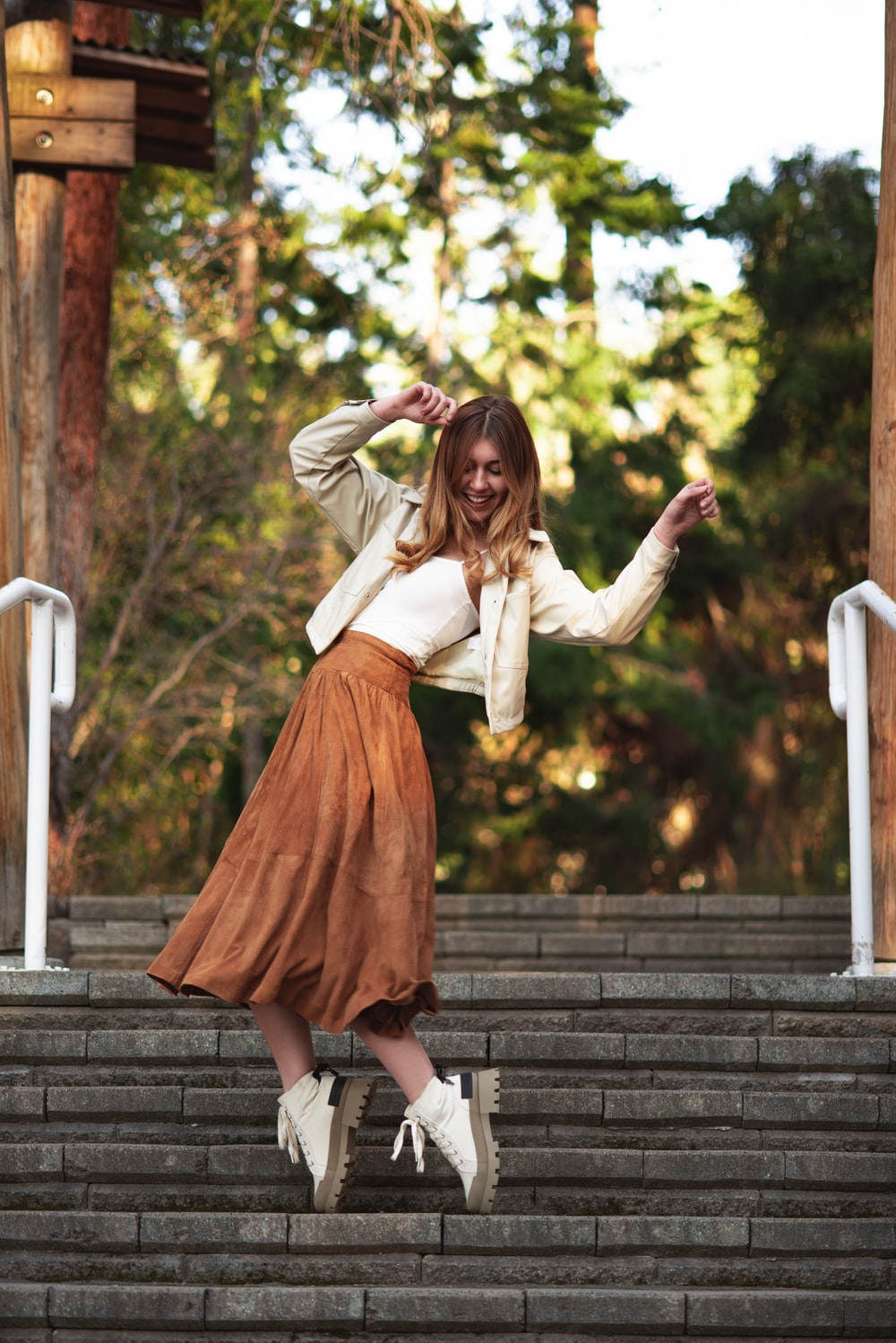 woman in white long sleeve shirt and red skirt sitting on white wooden bench