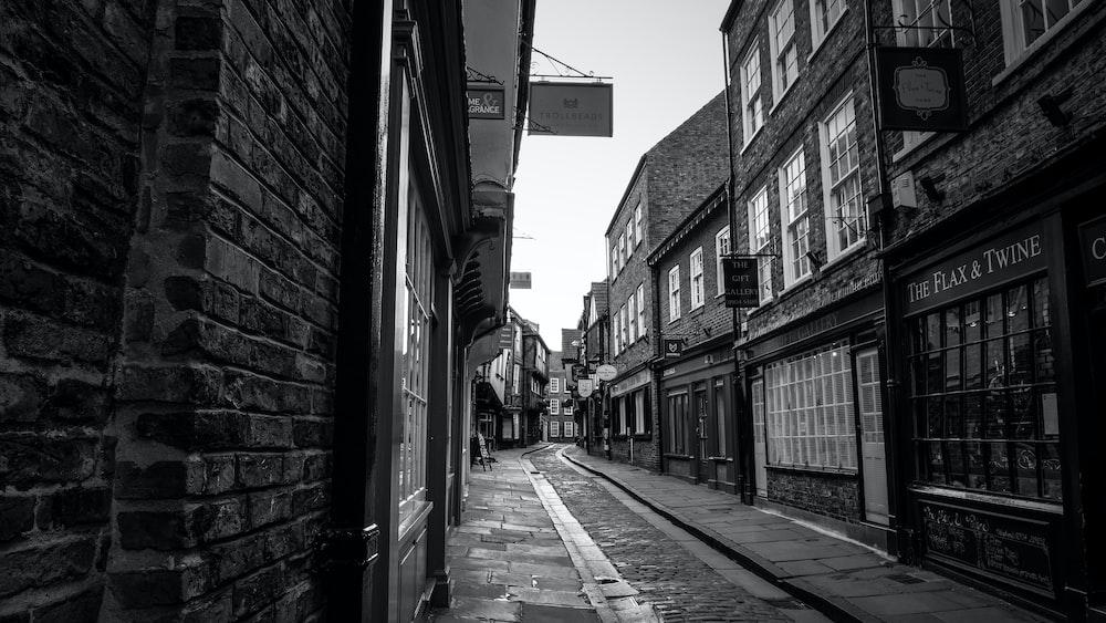 grayscale photo of empty street between buildings