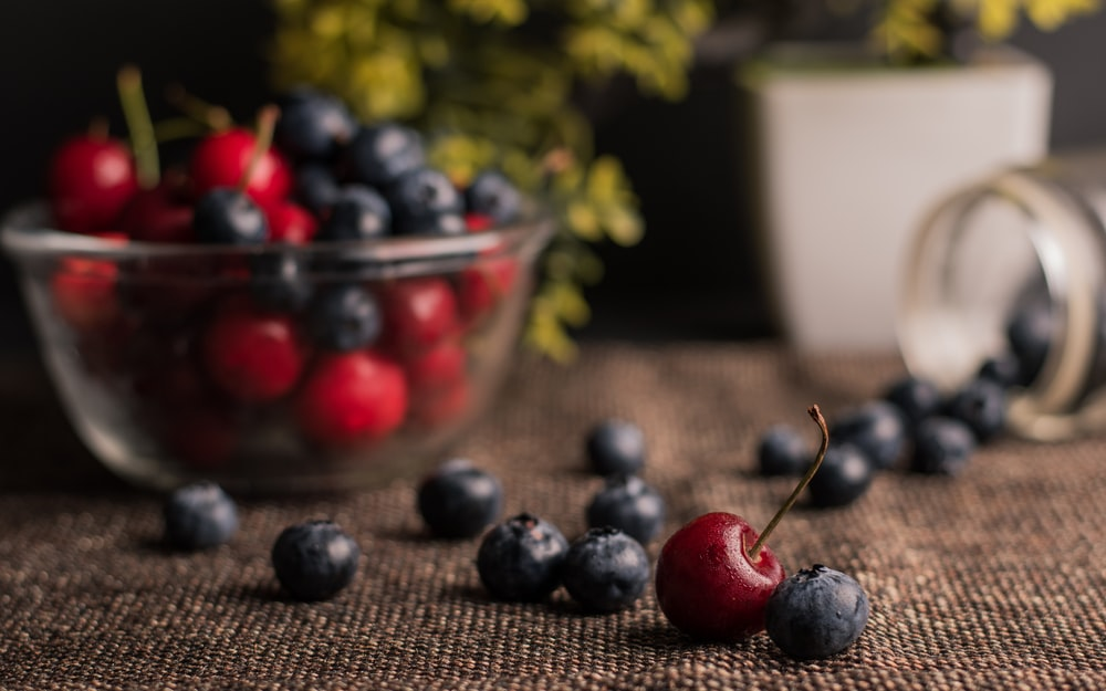 red and blue berries in clear glass bowl