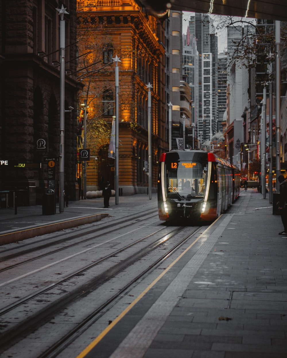 red and black tram on road between high rise buildings during daytime