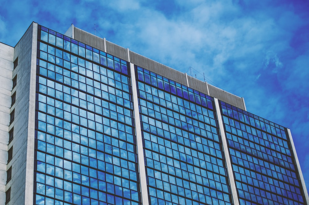 blue and white glass walled building under blue sky
