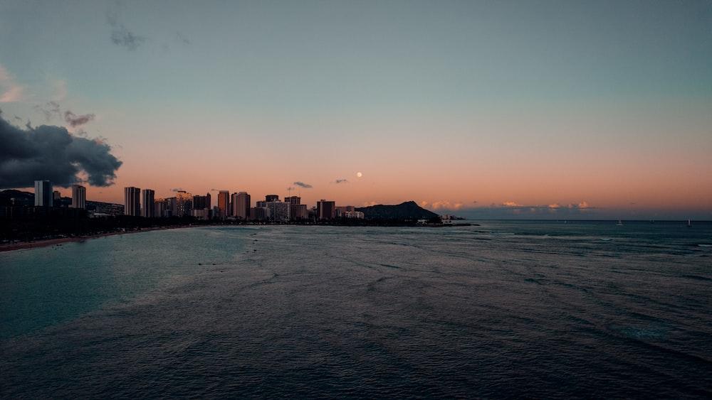 city skyline across the sea during sunset