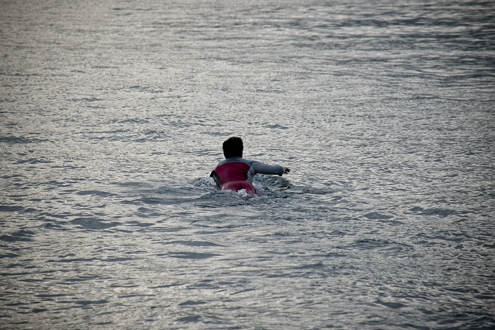 person in red shirt swimming on water during daytime