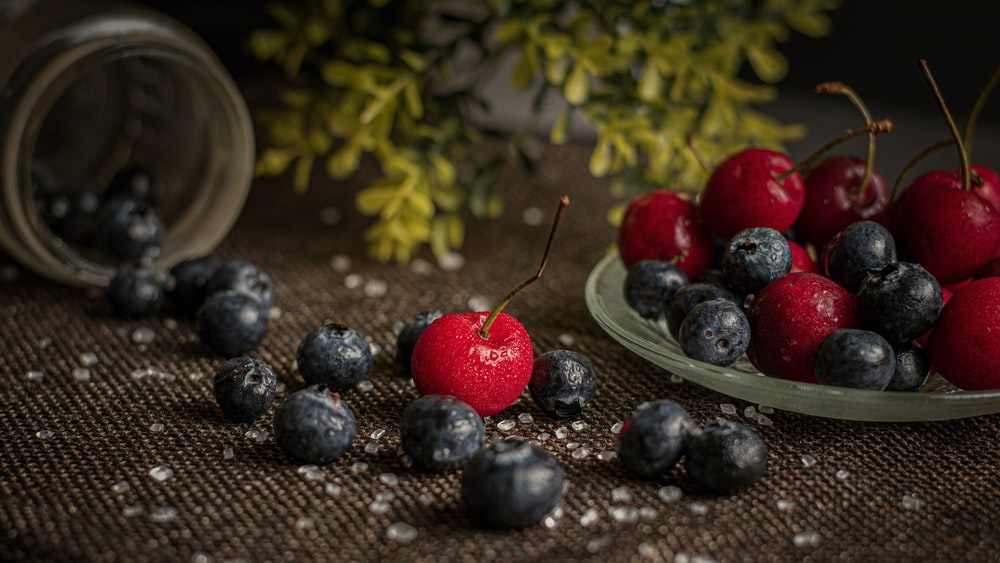 red and blue berries on stainless steel bowl
