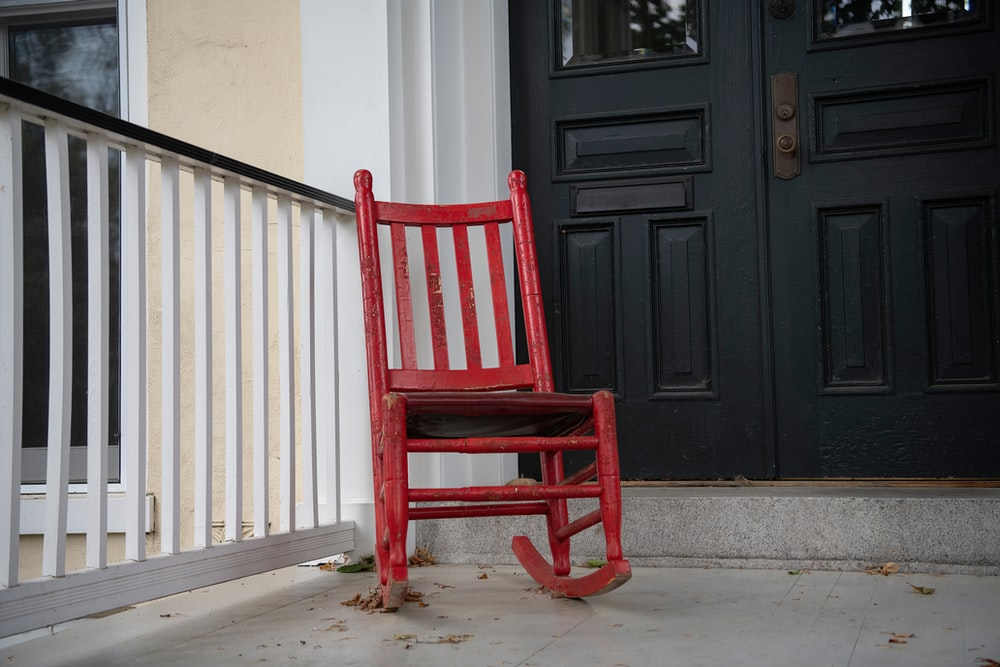 red wooden rocking chair near white wooden wall