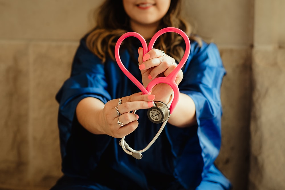 girl in blue jacket holding red and silver ring