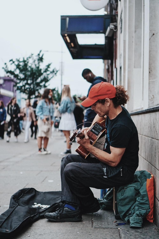 man in black t-shirt playing brown acoustic guitar