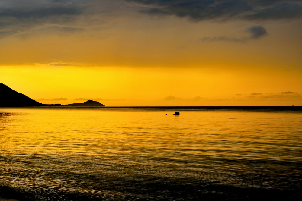 silhouette of mountain beside sea during sunset