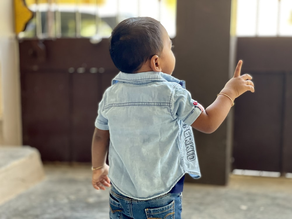 boy in blue denim dungaree standing on gray concrete floor during daytime