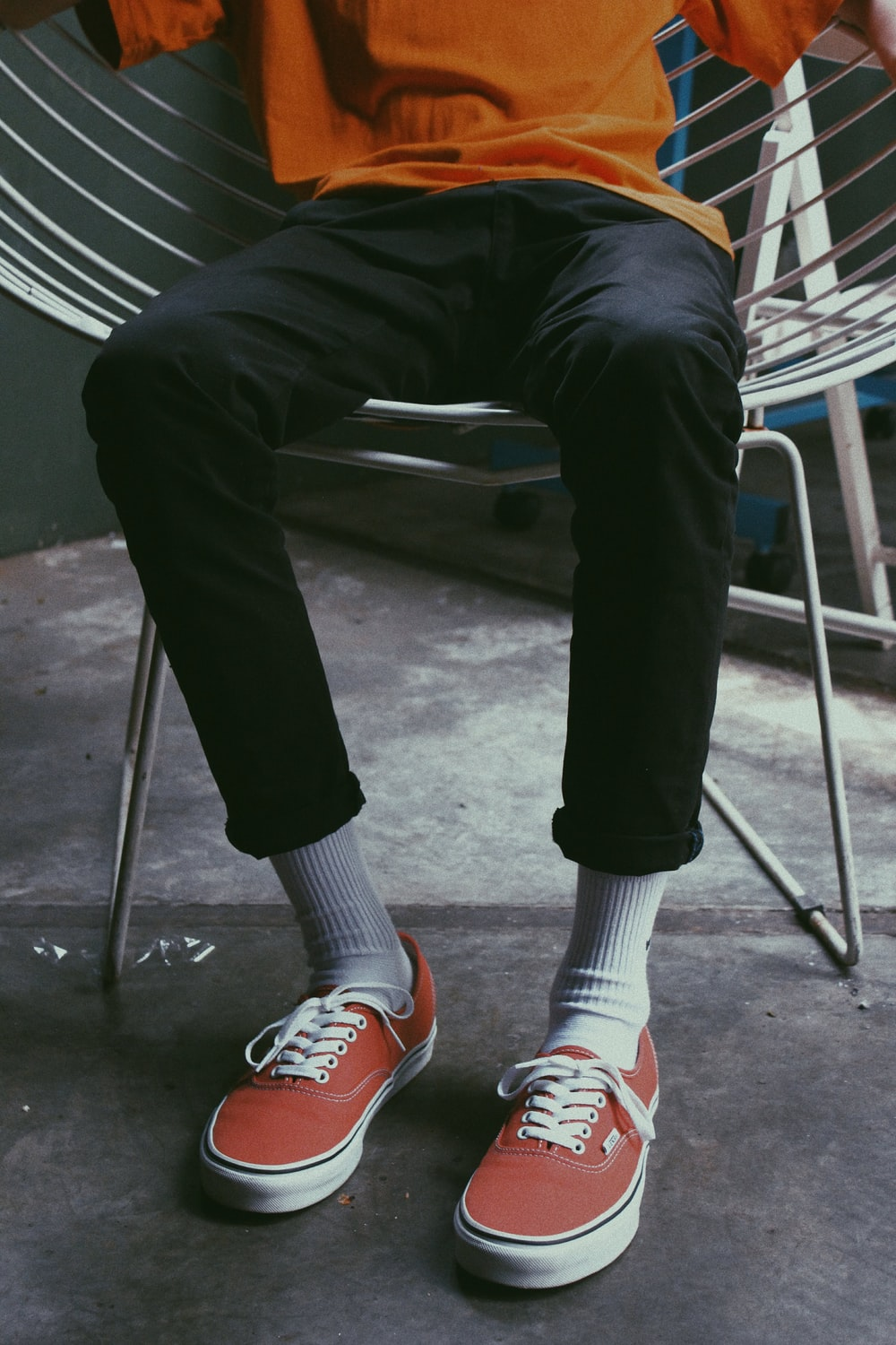 person in black pants and red and white sneakers