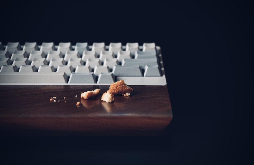white computer keyboard on brown wooden desk