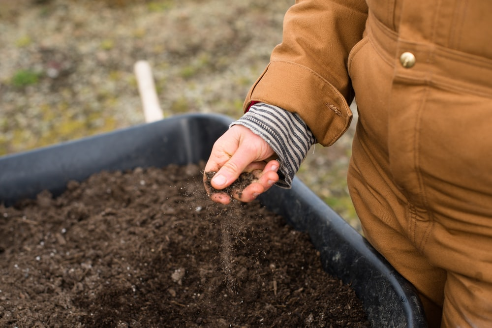person in yellow jacket holding black soil