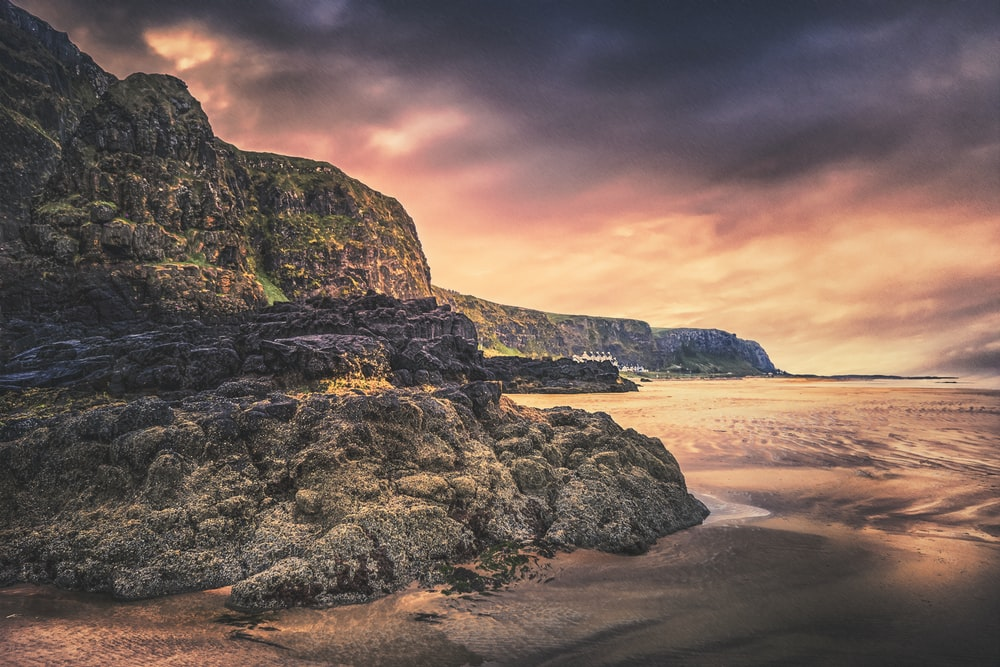 brown and green rock formation on beach during sunset