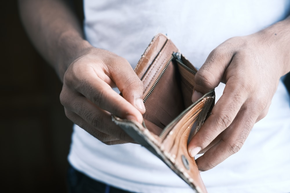 person holding brown leather bifold wallet